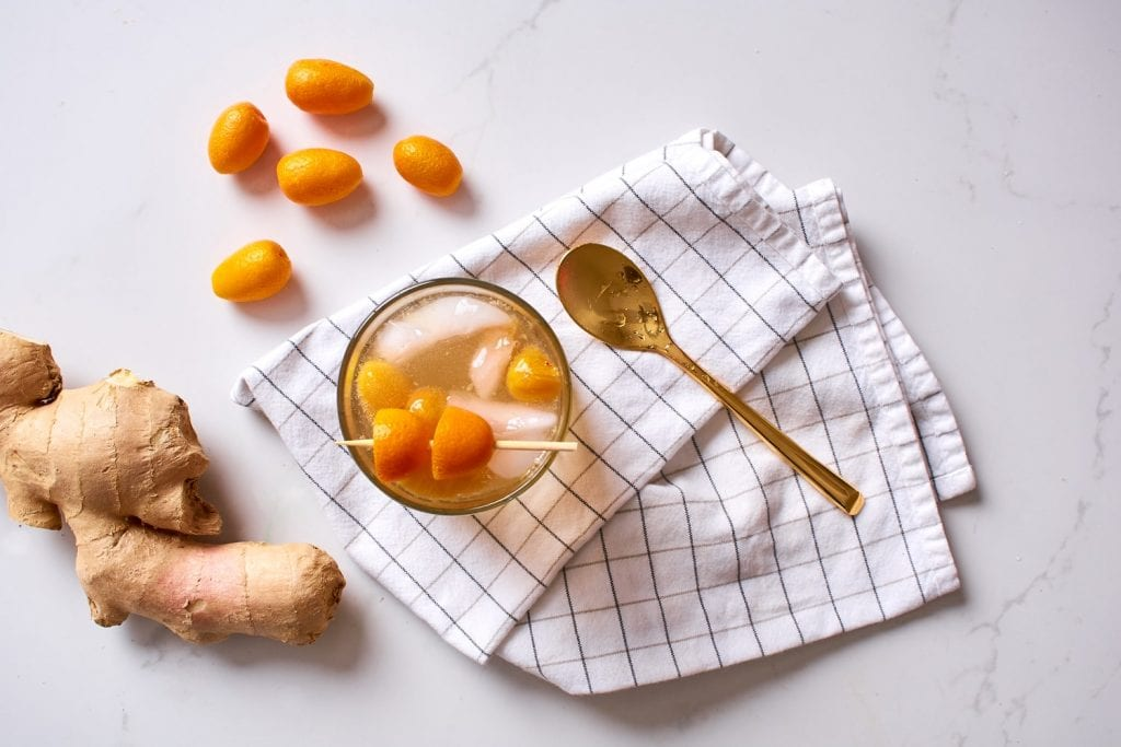 Rocks glass filled with kumquats, ginger, rum and club soda garnished with skewered kumquats. Spoon laid to the side of glass.